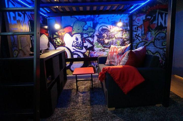 Die Wand gegenüber der Tür ist mit einem Graffiti verziert davor steht ein schwarzes Hochbett drunter stehen eine schwarze Couch und gegenüber ein Fehrnsehschrank  darauf ein  Samsung UE-55NU8009, LED-Fernseher schwarz mit SmartTV, HDMI, WLAN und PVR