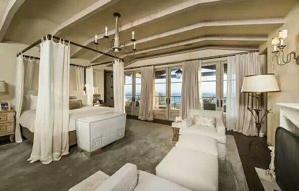 Un candelabro a los pies de la cama, sofás blancos, una cama matrimonial con cortinas del mismo color blanco, una chimenea junto a una lámpara de piso y un candelabro, un televisor de plasma