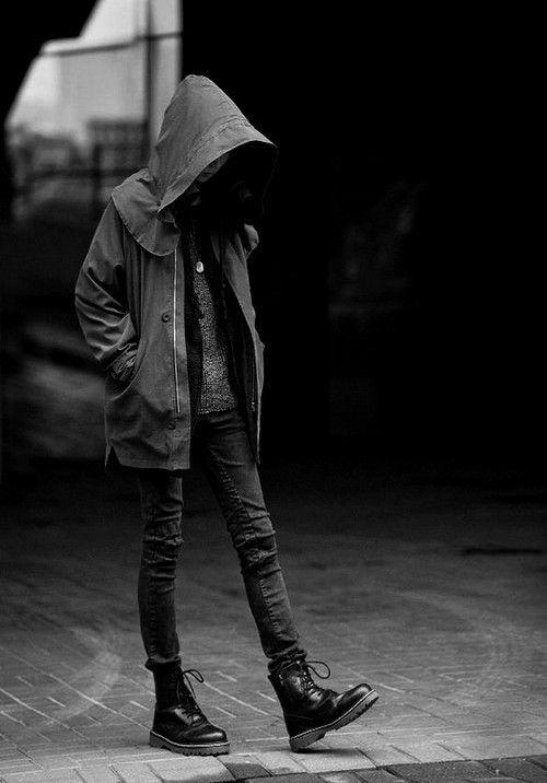 Muchacha joven paseando bajo la lluvia. Lleva una capucha que le tapa la cara, ropa vaquera y botas tipo militar negras.